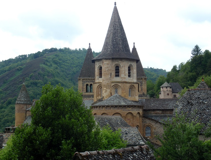 Stone turrets of Abbaye Sainte Foy rise above the trees