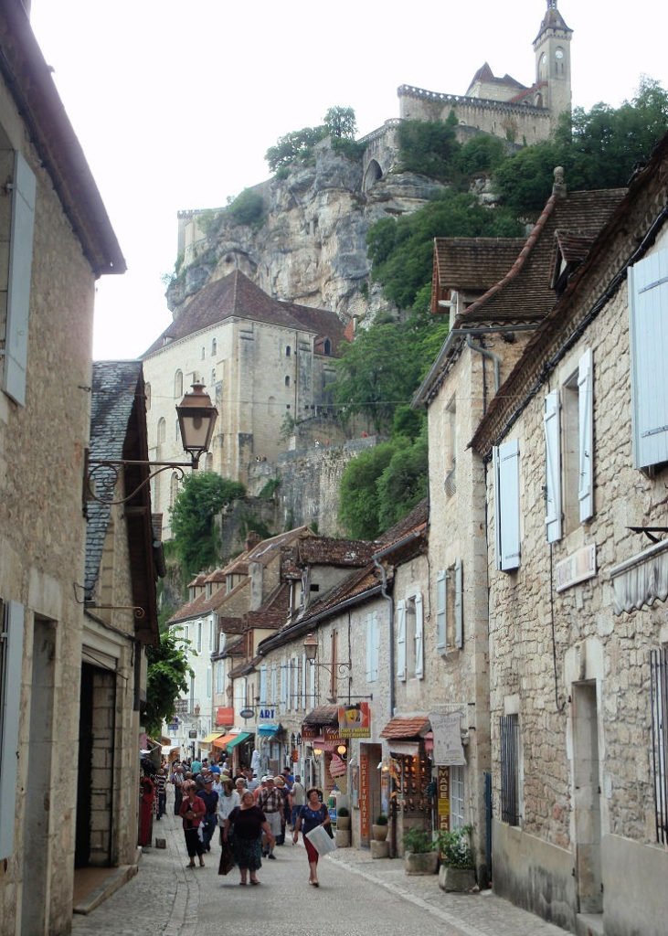 Ancient chapels carved into the cliff-face above shops lining the main street of Rocamadour