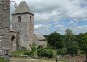 Stone church with adjoining bell tower set beside a green garden