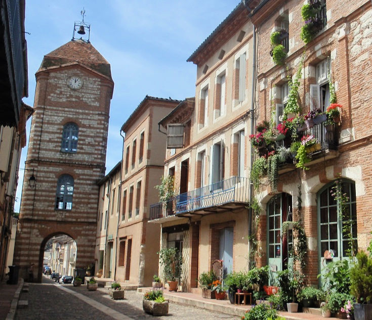 Four storey brick clock tower straddles the narrow street on the entrance to Auvillar
