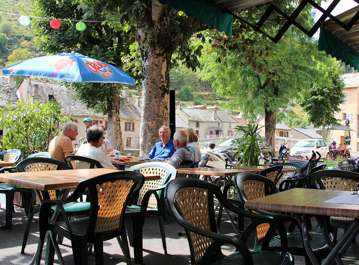 Customers relax over a cold drink at a Café in Le Pont-de-Montvert