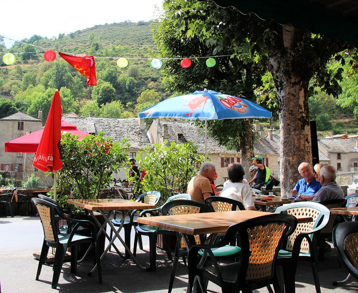 Customers sit at wooden tables under the shade of a large tree and a colourful umbrella