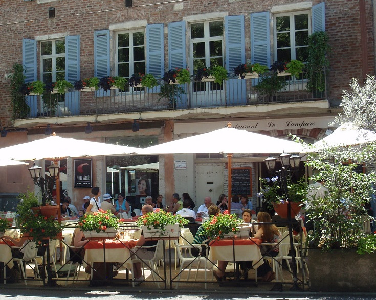 Café tables set outside under large beige umbrellas, in front of a pale brick building with light blue shuttered windows
