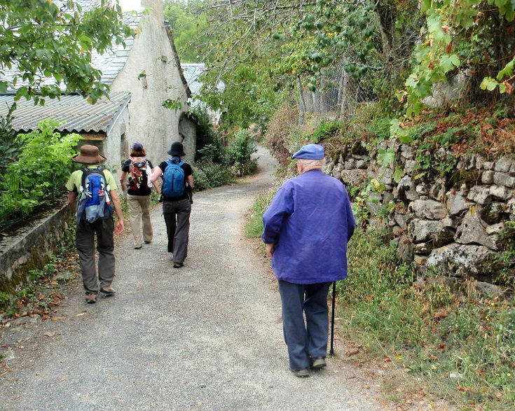 Frenchman in a beret follows three women long-distance walking through the village of Campuac