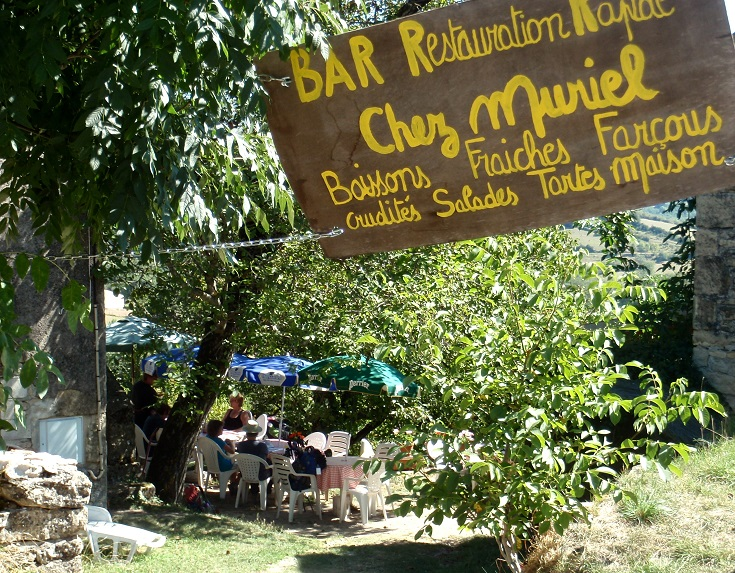 Chez Muriel sign with café tables behind under a tree