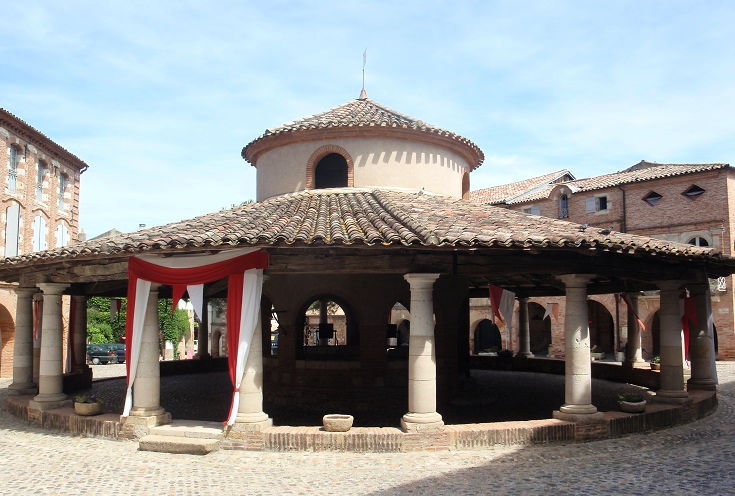Circular halle - stone columns, tiled roof covering an open area which hosts the weekly market in Auvillar