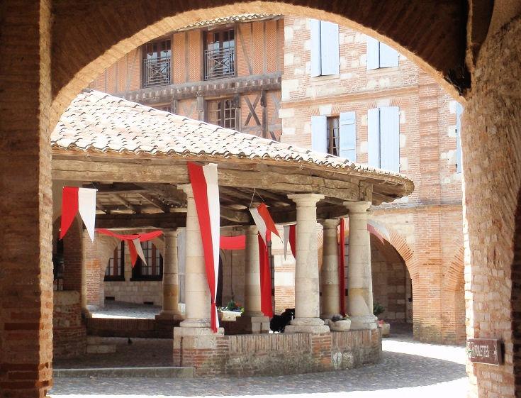 Circular halle in Auvillar, viewed through brick arches of an arcade