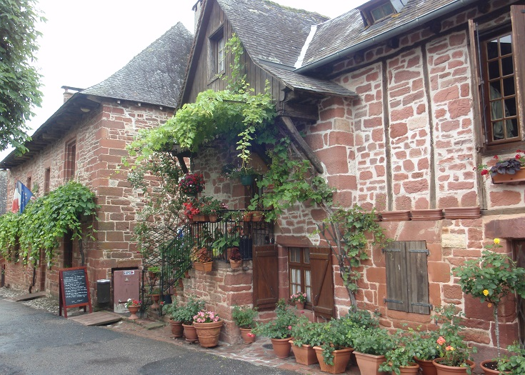 Dark red stone buildings with wisteria vines and colourful pot plants