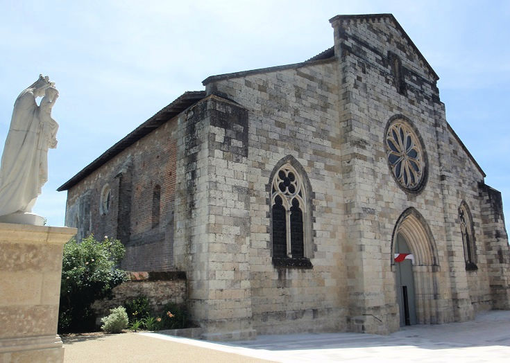 Eighteenth century stone front facade and brick side wall of the church in Auvillar