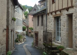 Crooked back street flanked with old stone and timber houses