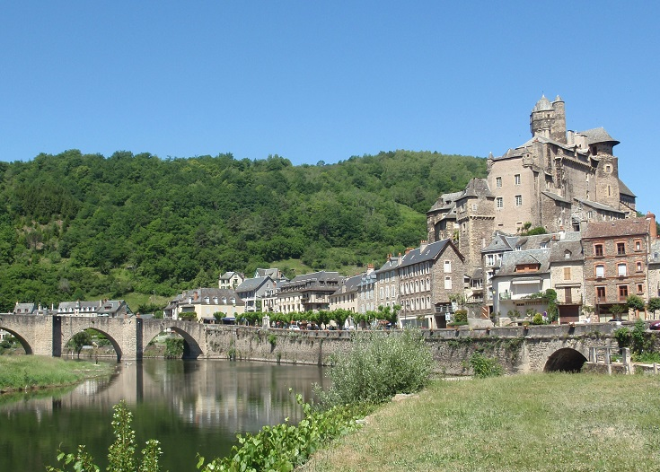 Stone houses, an imposing chateau and an arched bridge across the river, with a forested ridge in the background