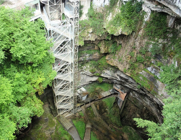 A steel cage stairway descends deep underground in Gouffre de Padirac, surrounded by rock and trees