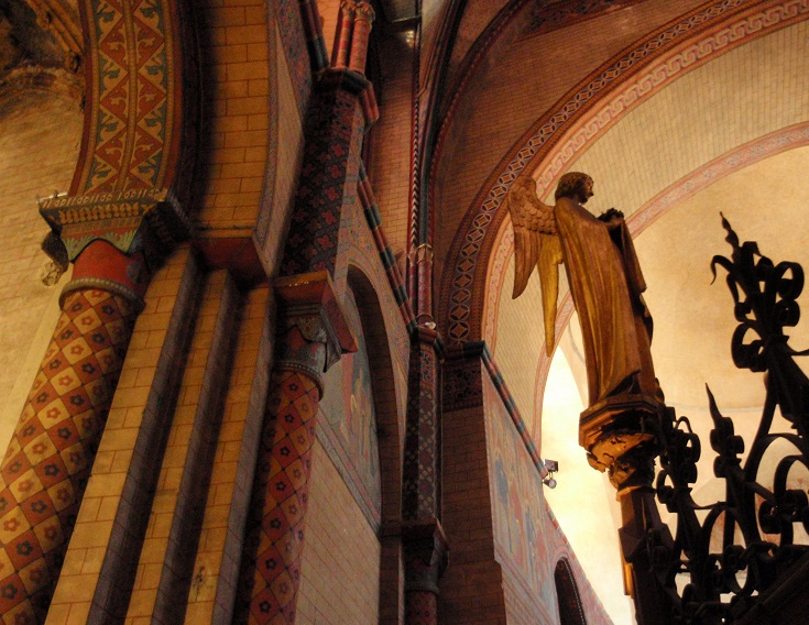 Interior walls of the cathedral in richly coloured yellows, golds and oranges