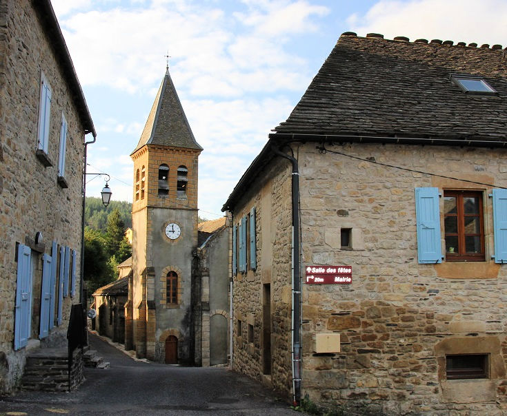 Tall church steeple and pale stone buildings in Le Bleymard