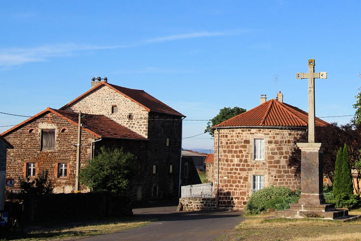 The curved rear brick facade of a church on the right, two brick houses to the left in Le Bouchet-Saint-Nicolas