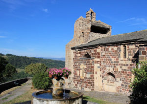 Stone church, flower-topped water fountain, views over the wooded hillside