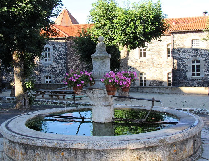 Water fountain decorated with flowers in the market place of Le Monastier-sur-Gazeille
