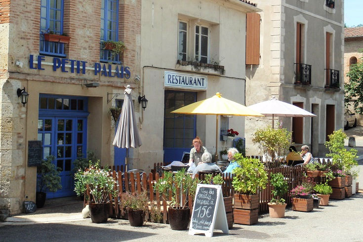 Outdoor café with tables, potted shrubs and shady umbrellas
