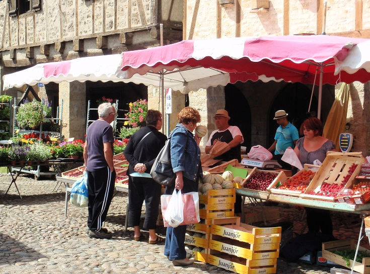 Customers inspect trays of fresh fruit at the Saturday morning market in Bretenoux