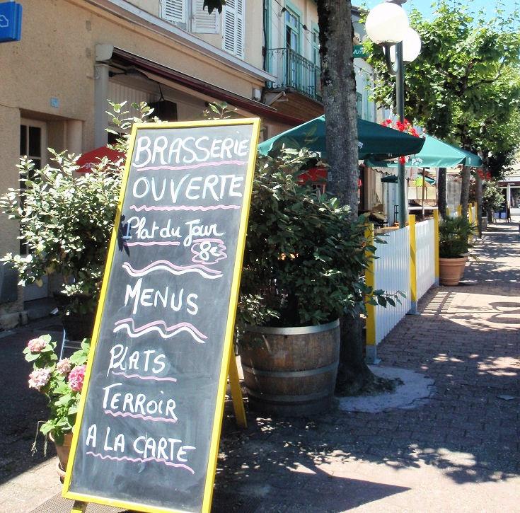 Café blackboard, pot plants screening tables at a café in Nogaro