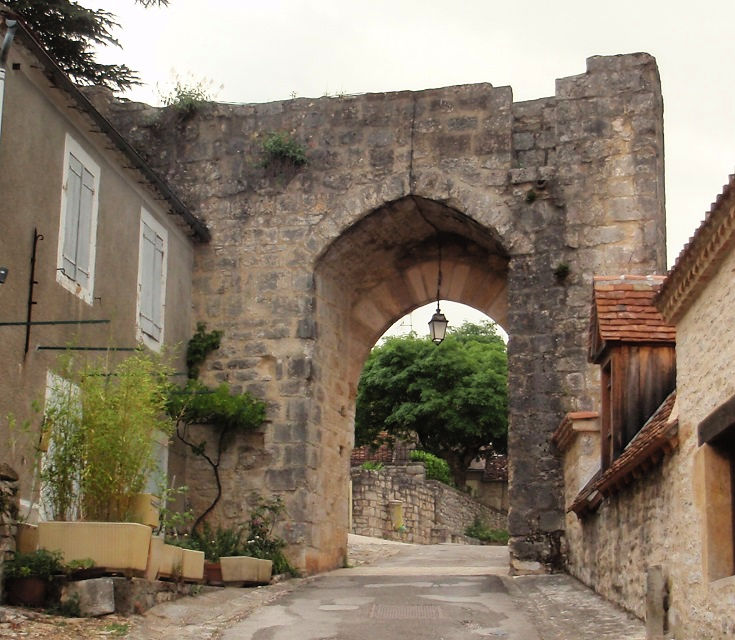 Ancient stone wall with an arched entrance allowing access to travellers