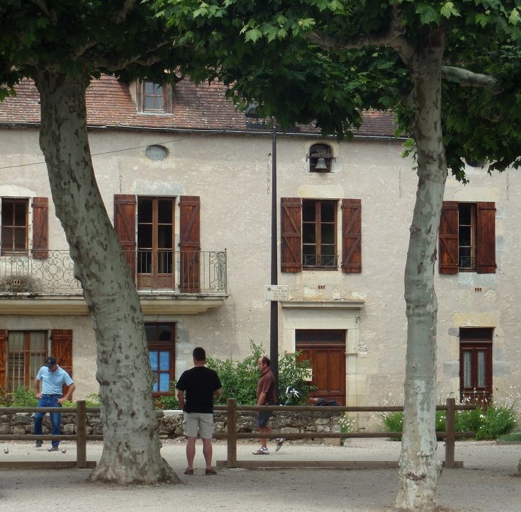 Three men play petanque under the shade of the plane trees