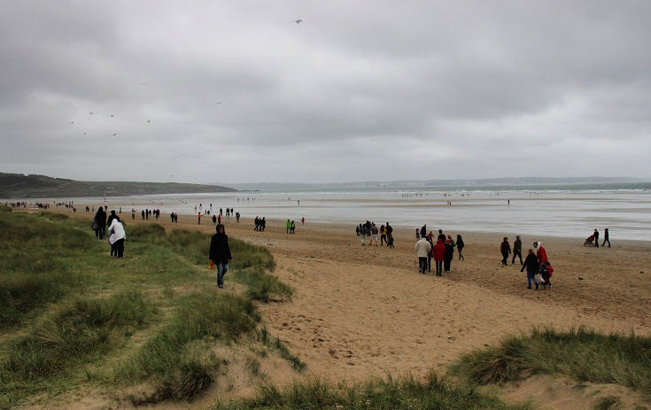 Beach goers on a cold, damp Sunday afternoon