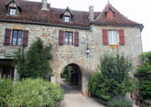 Turreted stone building which serves as a gateway to the village of Loubressac through an arched entrance. Brown shutters adorn windows on the upper level