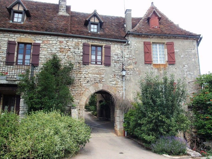 Pale stone arched gate built into a two-storey stone wall, windows with brown shutters