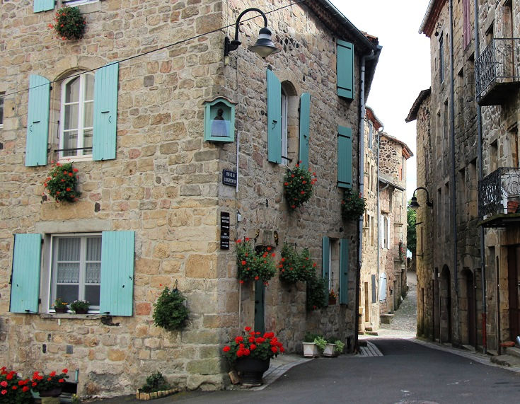 Stone house with pale blue shutters in Pradelles