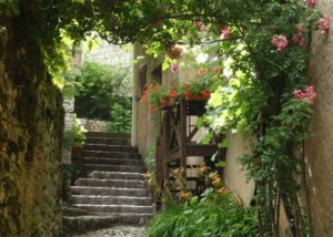 Narrow laneway with stone steps and a wooden water wheel hung with bougainvillea and other flowering plants