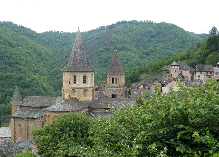 View of the abbey turrets and rooftops of Conques amongst the trees