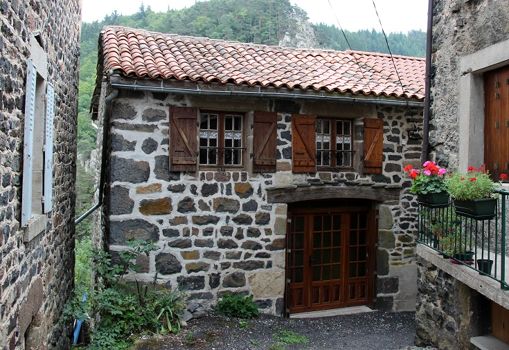Village house in Saint-Privat-d'Allier built from dark stone with crisp white mortar and wooden shutters