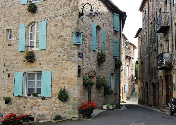 Bright blue shutters and flowering plants adorn a stone house in Pradelles