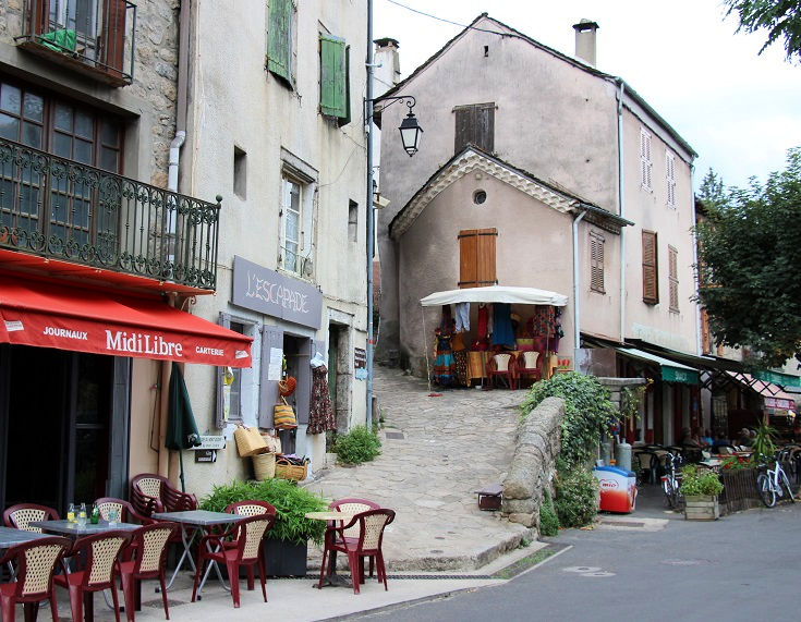 Café tables, colourful awnings and shop fronts line a narrow street