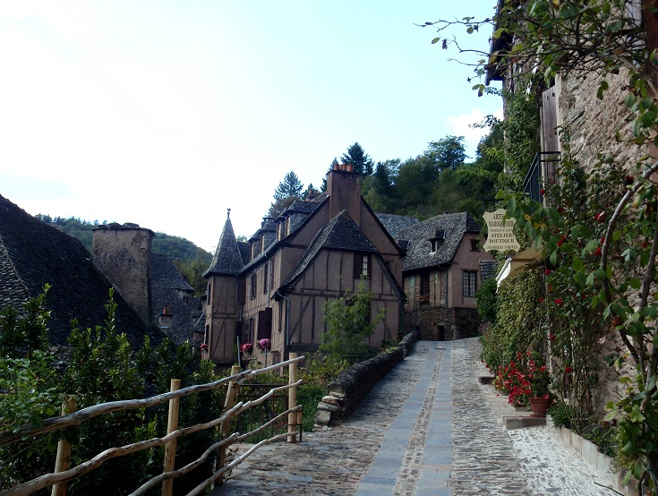 Street lined with houses climbing the hill in Conques