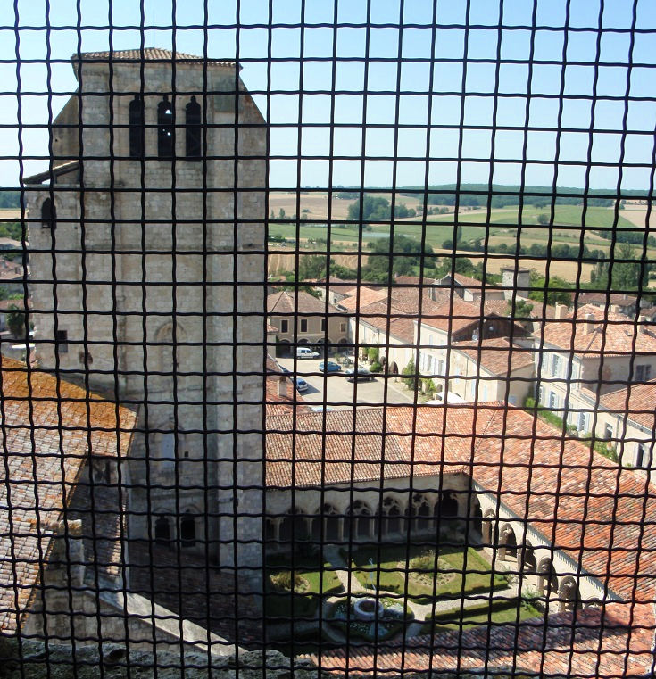 View from Tour Belvedere through the security screen of the cloister and village streets of La Romieu, and the Cardinal's Tower