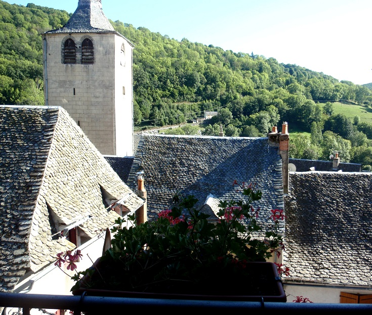 Tiled rooftops, Church bell tower and tree covered ridge surrounding Saint-Chély-d'Aubrac