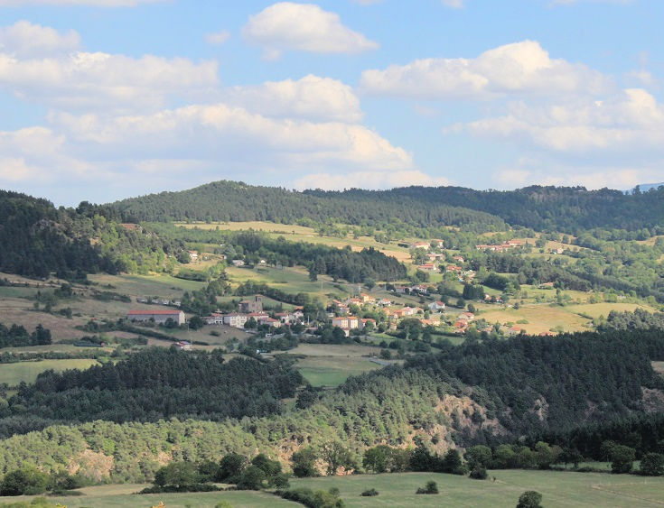 Distant view of a small town nestled on the side of a hill among green fields and pockets of forest.