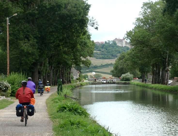 Cyclists on the Burgundy Canal with Châteauneuf-en-Auxois in the distance